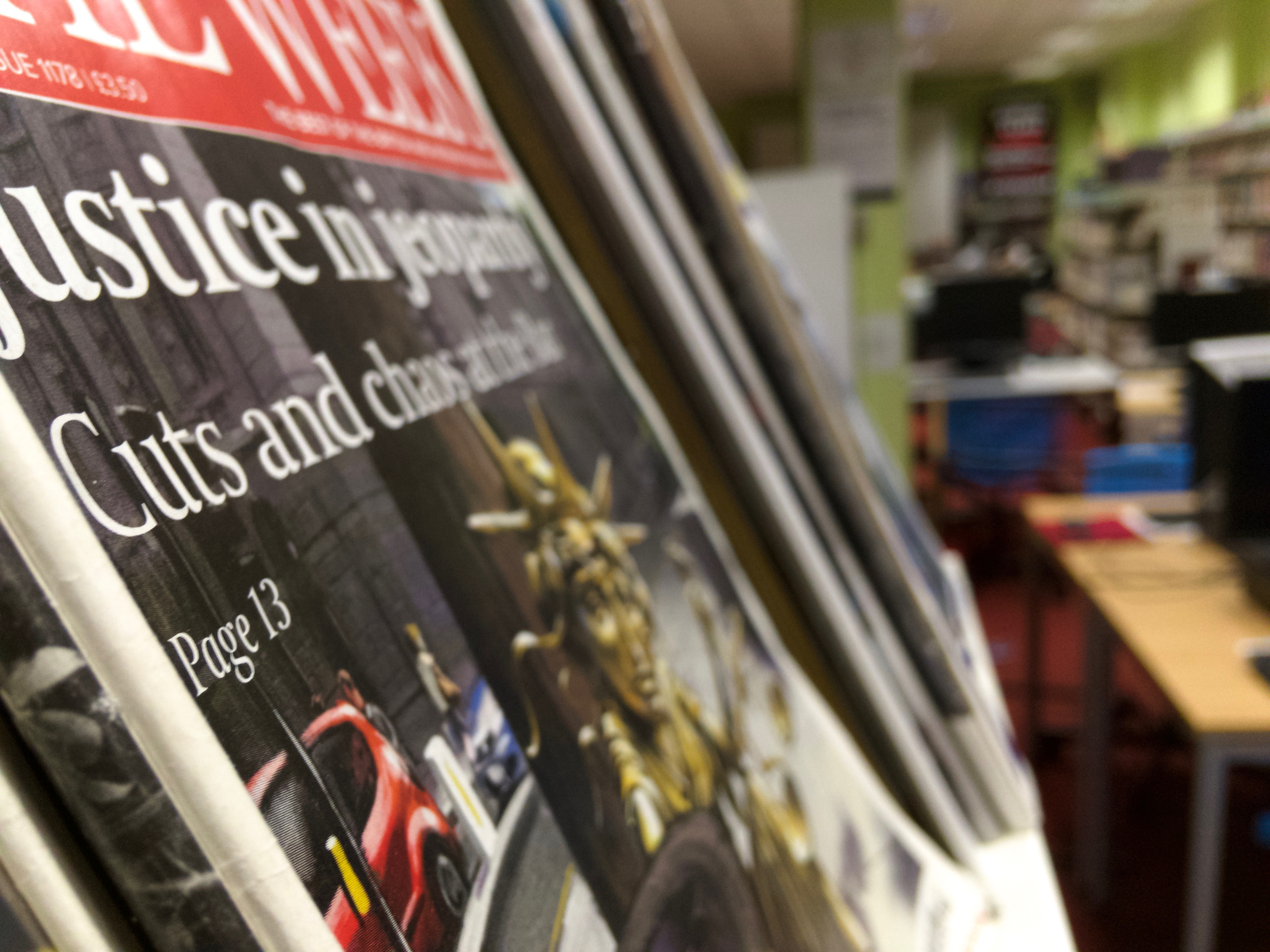 Close-up of magazine in a library shows front-page about government cuts