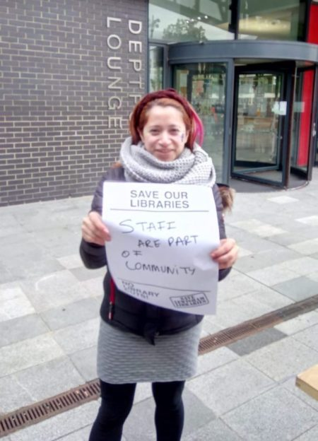 Woman holds sign
